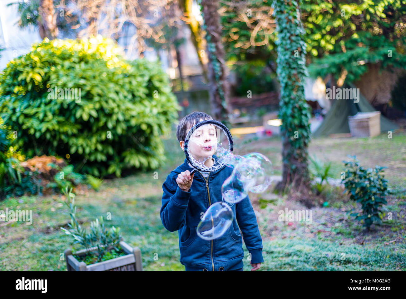 7-year-old child outdoors in the garden in winter makes big soap bubbles Stock Photo