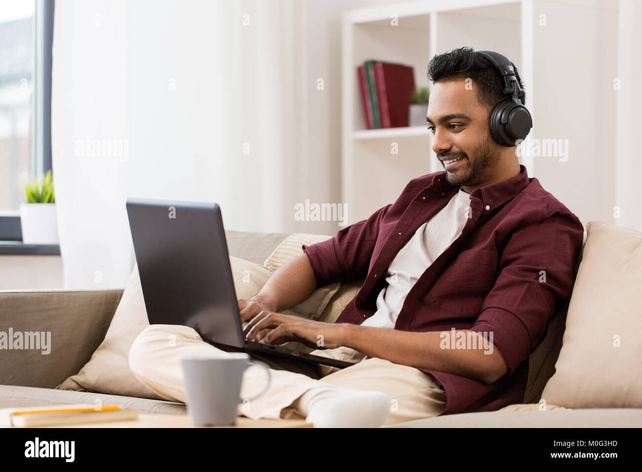 man in headphones with laptop listening to music - Stock Image
