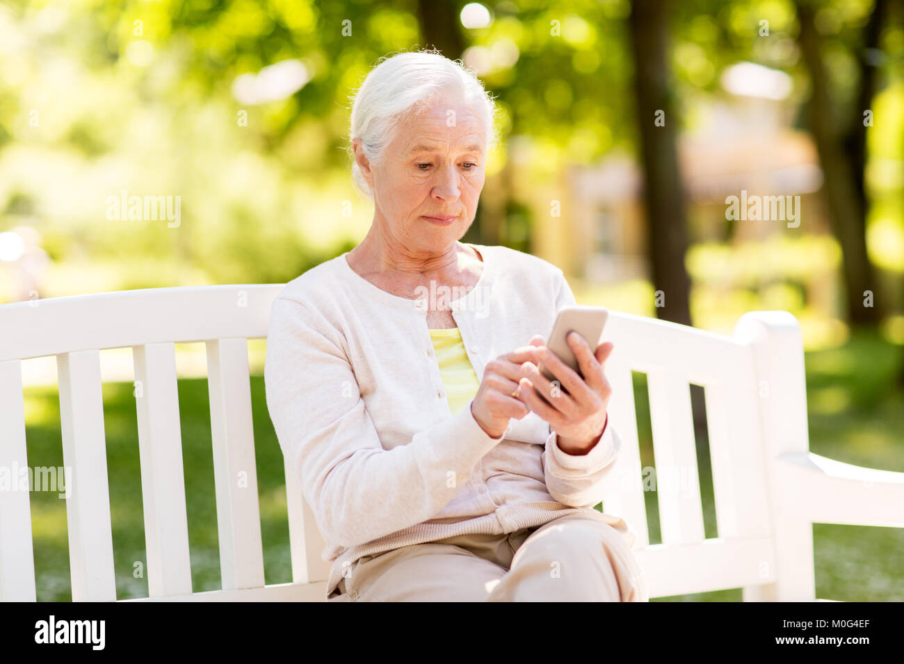 senior woman with smartphone at summer park - Stock Image