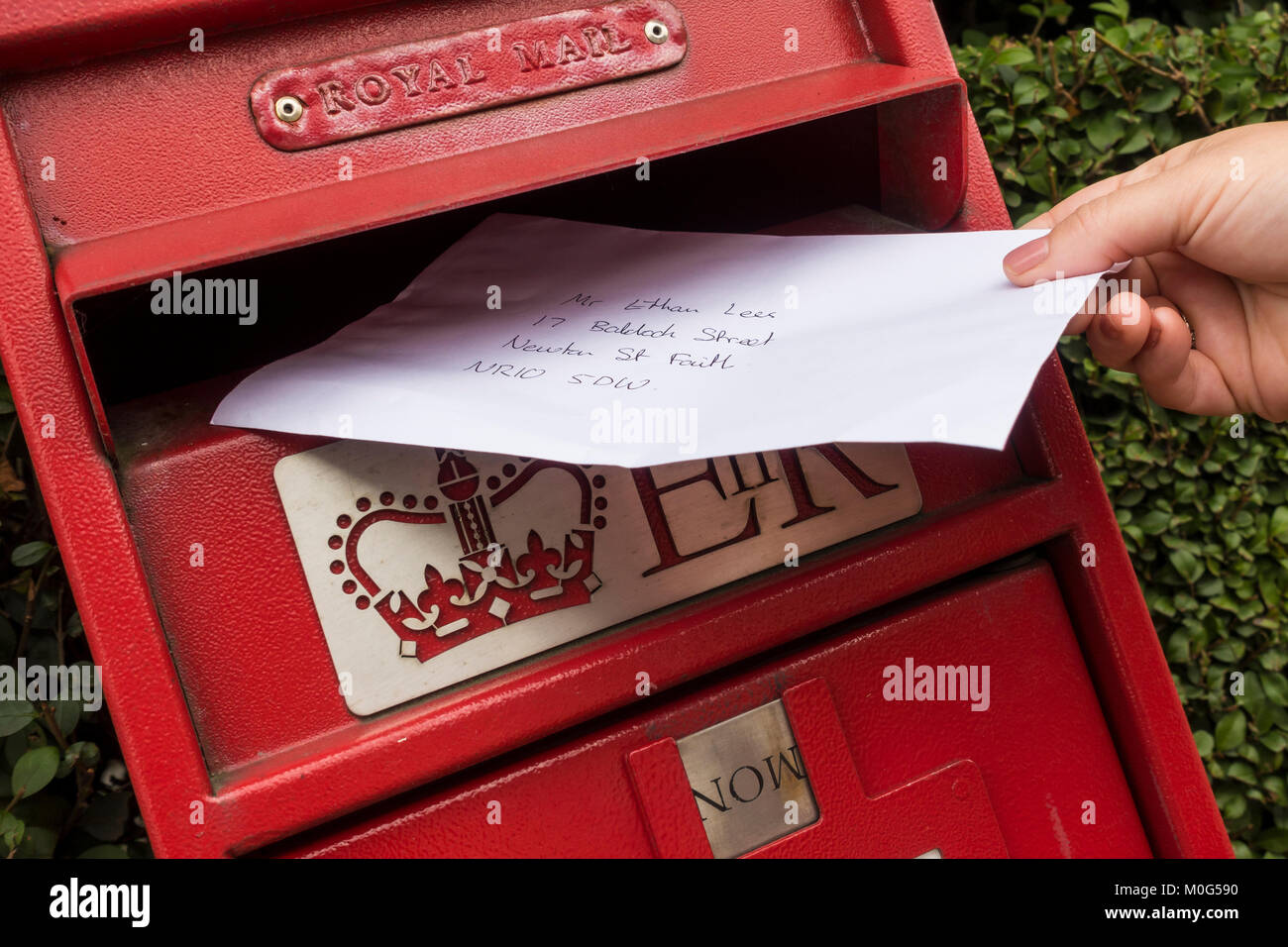 Letter being posted in a red Royal Mail post box - Stock Image