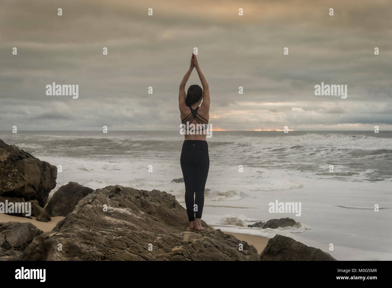 woman doing yoga on rocks by the sea, standing lotus position. - Stock Image