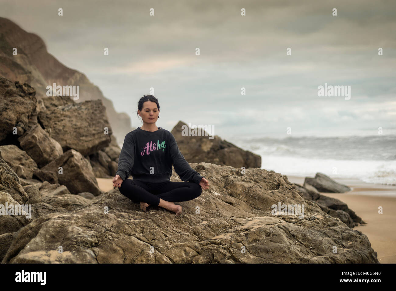 woman doing yoga sitting on a rock by the sea, lotus position. - Stock Image