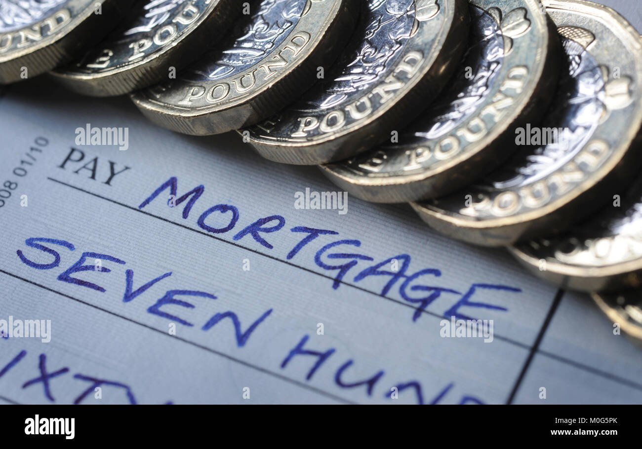 CHEQUE BOOK AND ONE POUND COINS WITH 'MORTGAGE' PAY NAME RE MORTGAGES INTEREST RATES INFLATION ETC UK - Stock Image