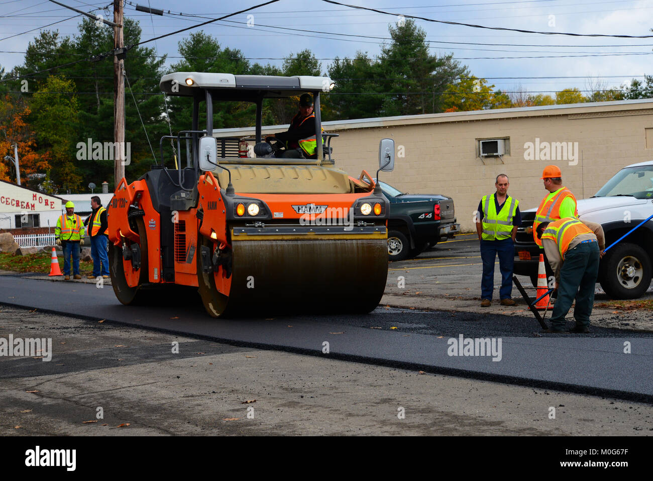 A road crew and equipment resurfacing a street in Speculator, NY USA - Stock Image