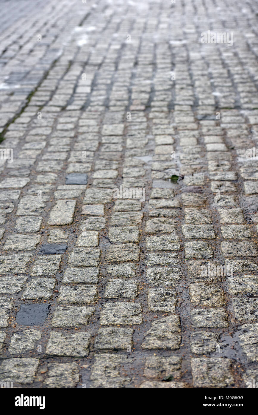 A wet cobbles street in an old and original part of a town. Historic methods of surfacing or building roads. Cobble - Stock Image