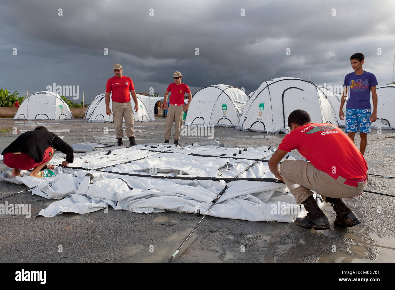 Members of Alegoas Fire Brigade assist in setting up tnets at Uniao Dos Palmares - Stock Image