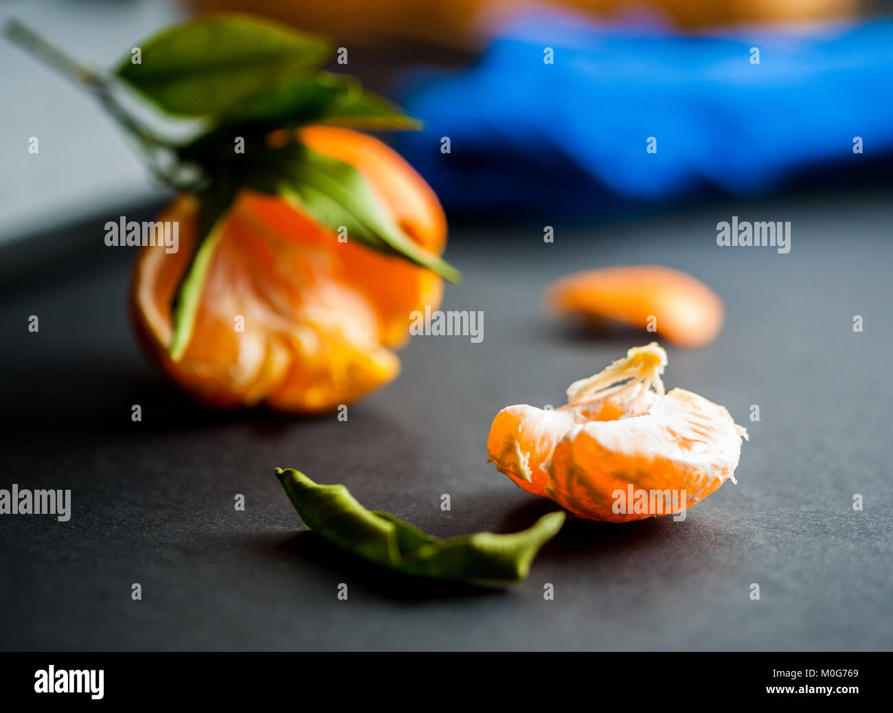 A close-up of a fresh juicy clementines with green leaves - Stock Image
