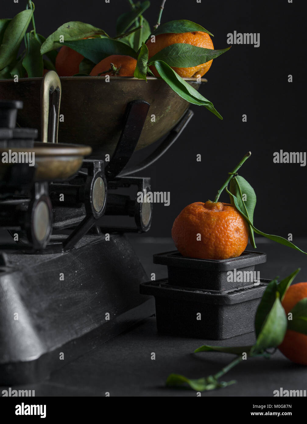 A bunch of fresh juicy clementines with green leaves in a scalepan and on a black table - Stock Image