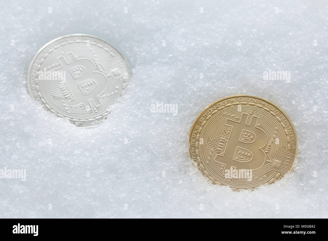 gold bitcoin on cold winter snow background - Stock Image