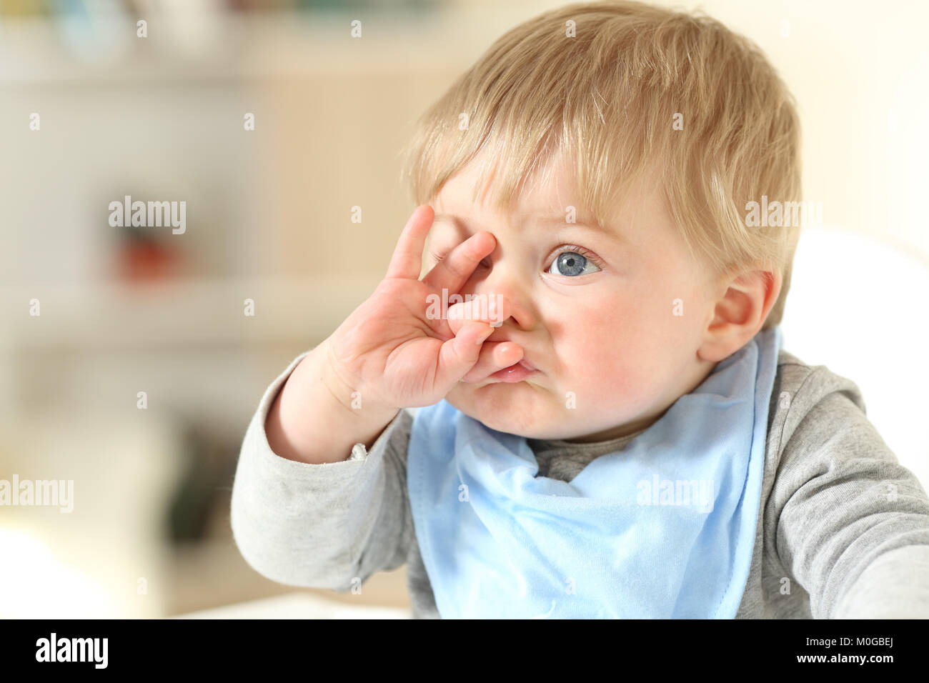 Portrait of a cute baby grimacing with a hand on the face at home - Stock Image