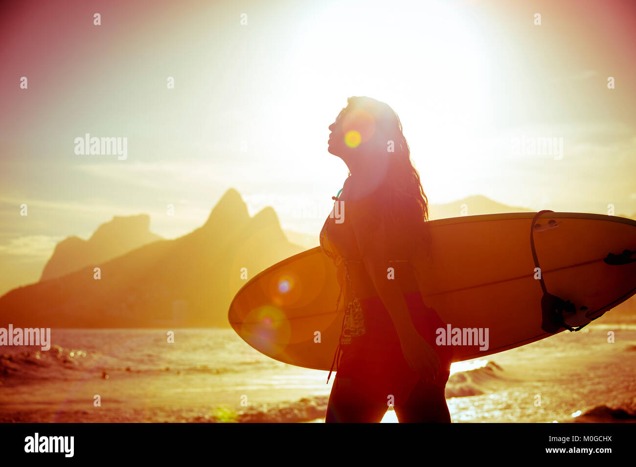 Unrecognizable silhouette of female surfer walking with her surfboard at Arpoador, the popular surf break in Rio - Stock Image
