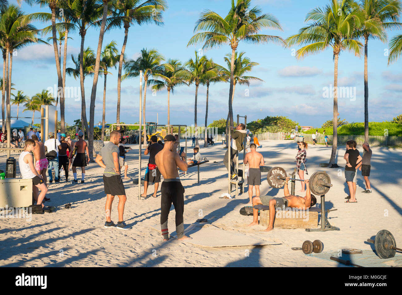 MIAMI - DECEMBER 27, 2017: Muscular young men attract onlookers working out at the outdoor workout station in Lummus - Stock Image
