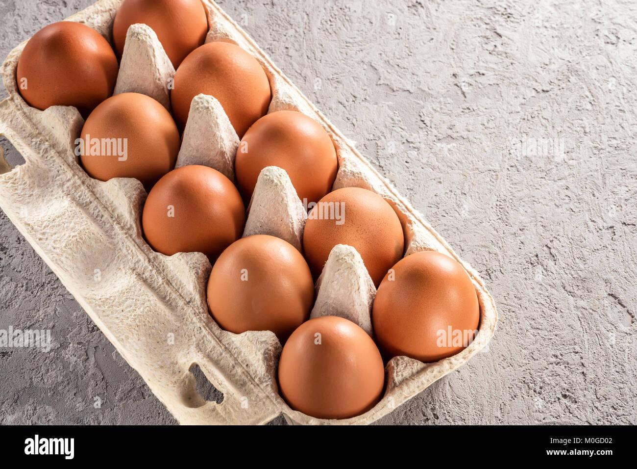 Farm raw fresh egg in pack on gray table scrambled eggs omelet fried egg - Stock Image