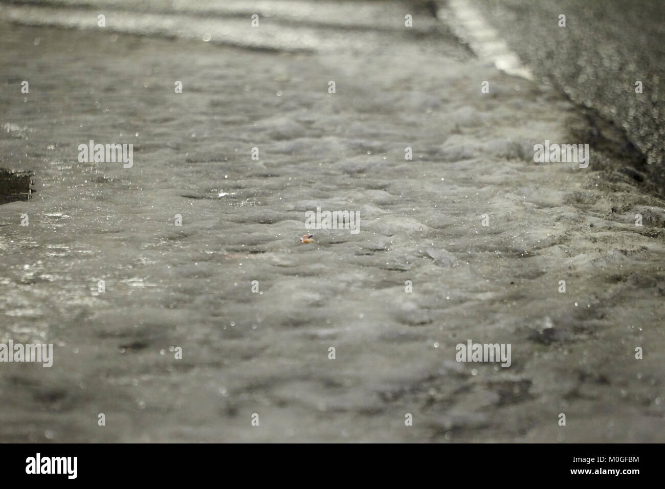 slippery ice and compacted snow covered path under streetlights at night in the uk Stock Photo