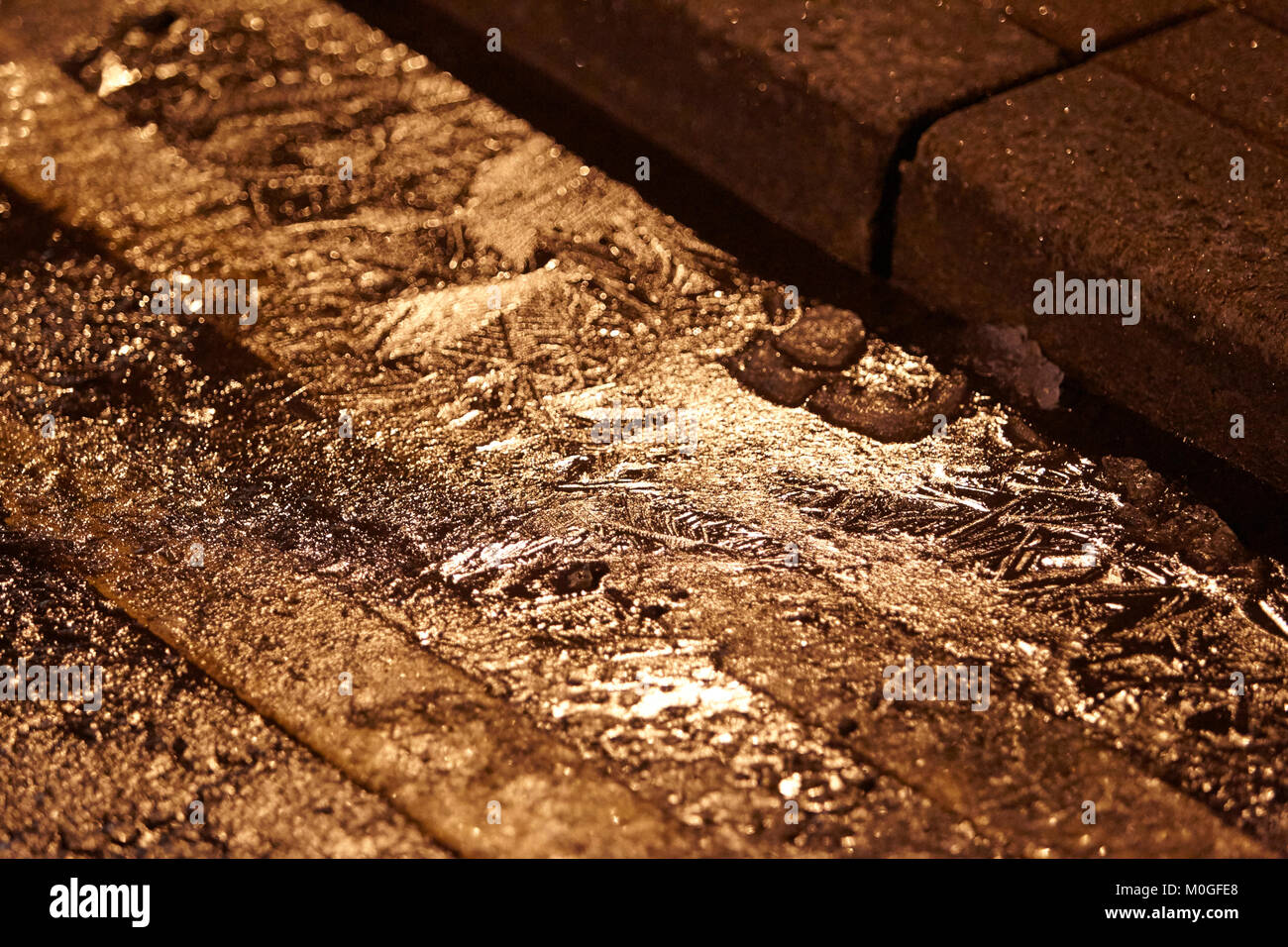 ice forming on water in gutter on road with double yellow lines at night in the uk - Stock Image