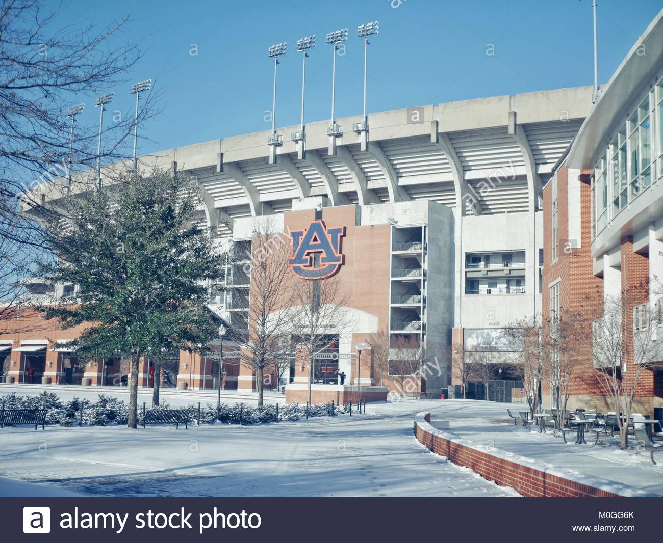 Snow day on a college campus in the southeast with a football stadium in the background. - Stock Image