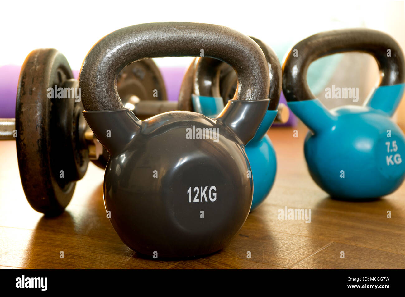 Kettlebells and dumbbells on a wooden floor - Stock Image