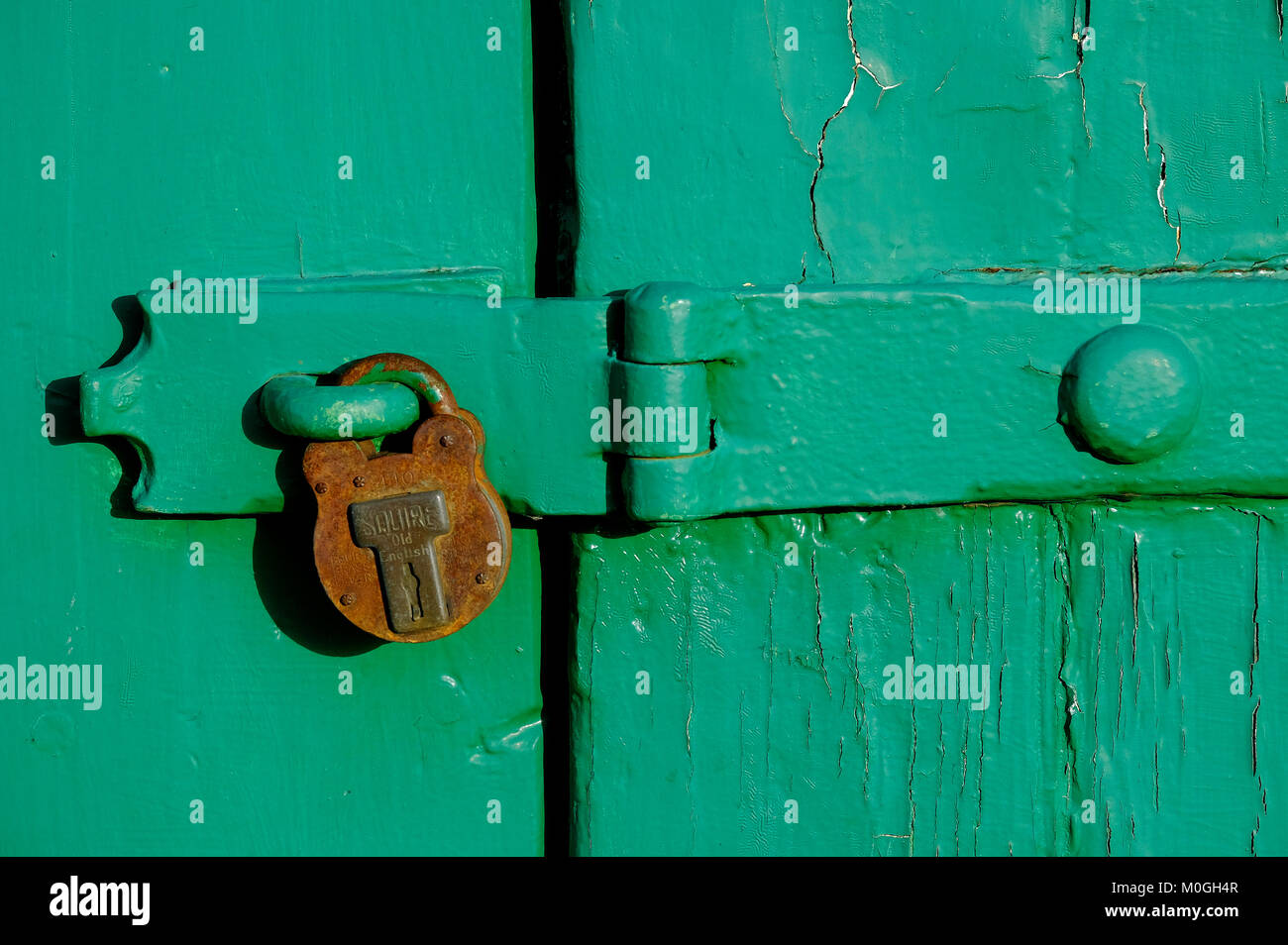 old rusty padlock on green painted garage door, norfolk, england Stock Photo