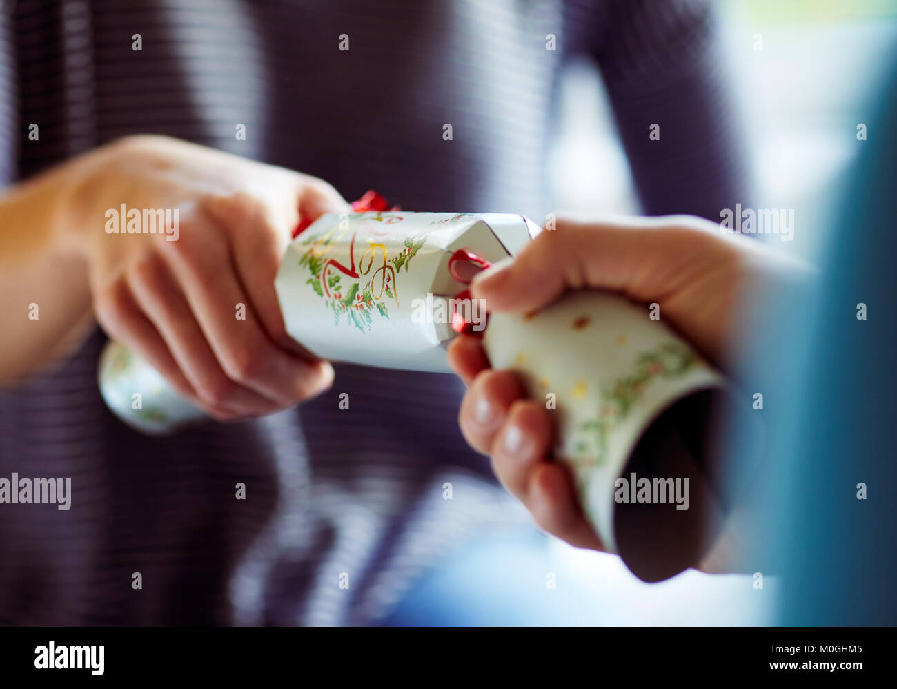 Two people pulling a Christmas cracker - Stock Image
