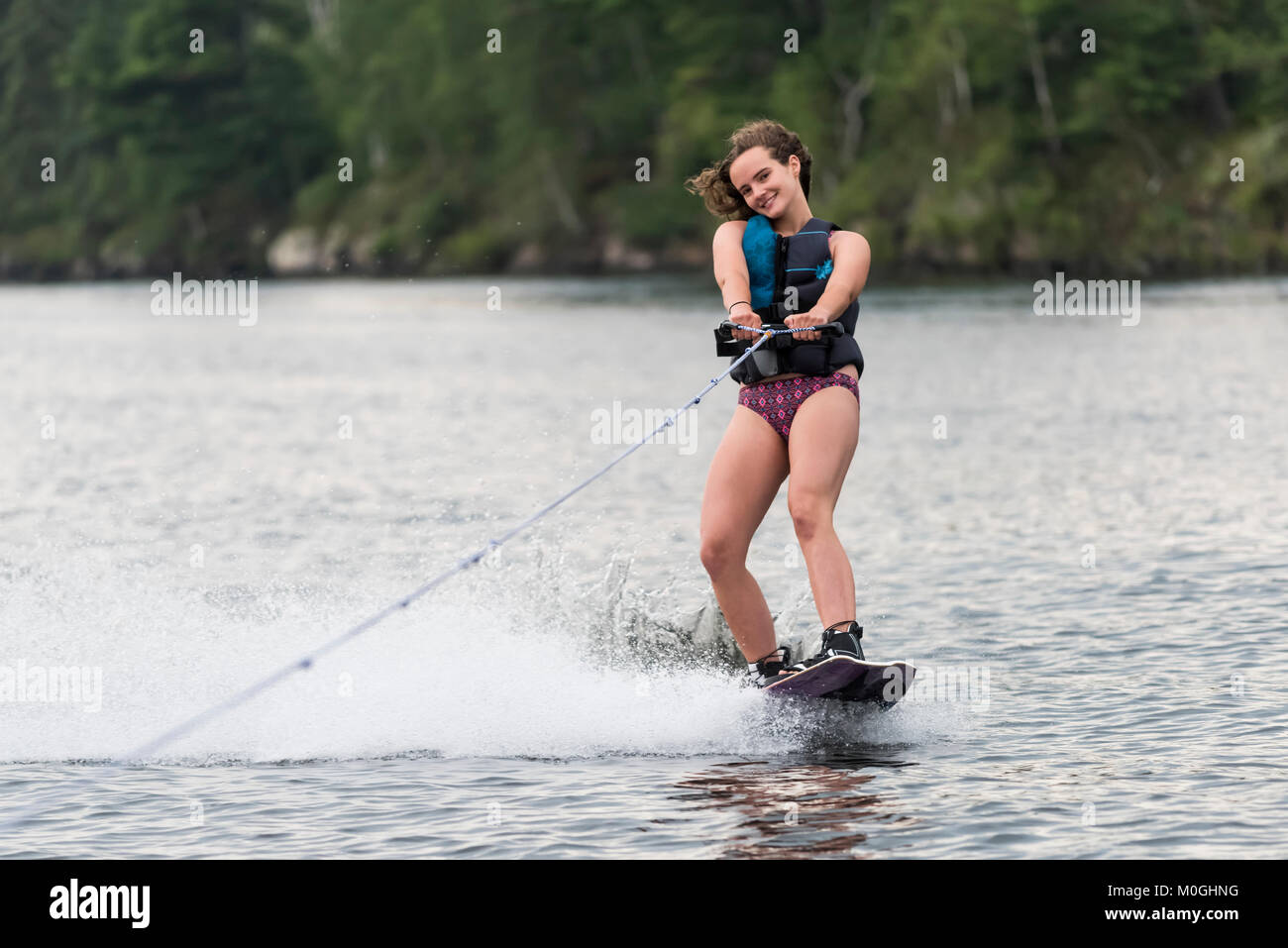 A teenage girl wakeboarding behind a boat on a lake; Lake of the Woods, Ontario, Canada - Stock Image