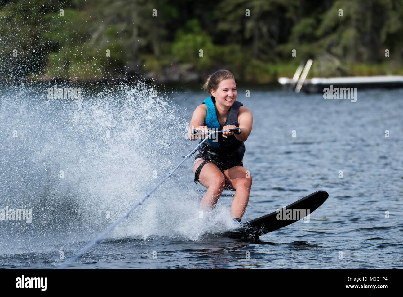 A young woman wakeboarding behind a boat on a lake; Lake of the Woods, Ontario, Canada - Stock Image
