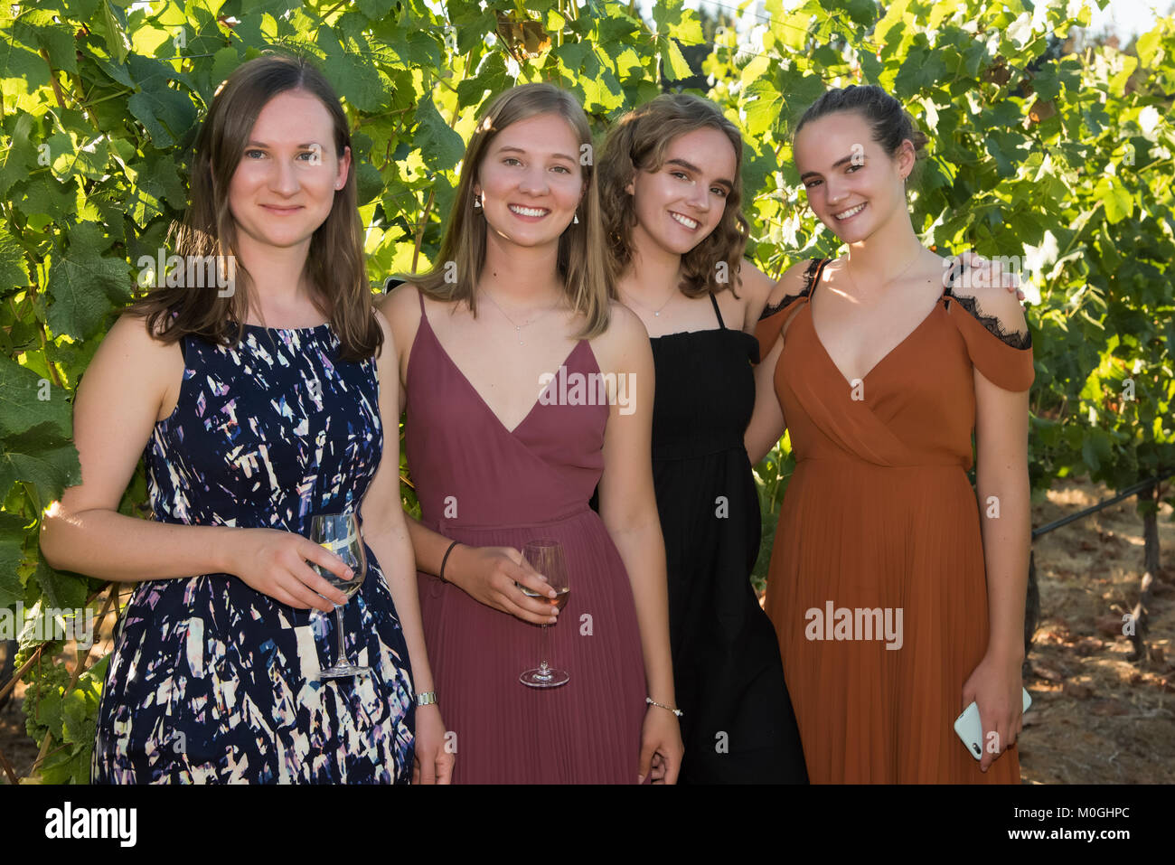 Portrait of four young women dressed in formal wear and holding glasses with drinks; Cobble Hill, British Columbia, - Stock Image