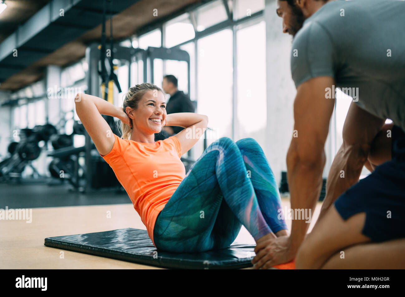 Personal trainer assisting woman lose weight - Stock Image