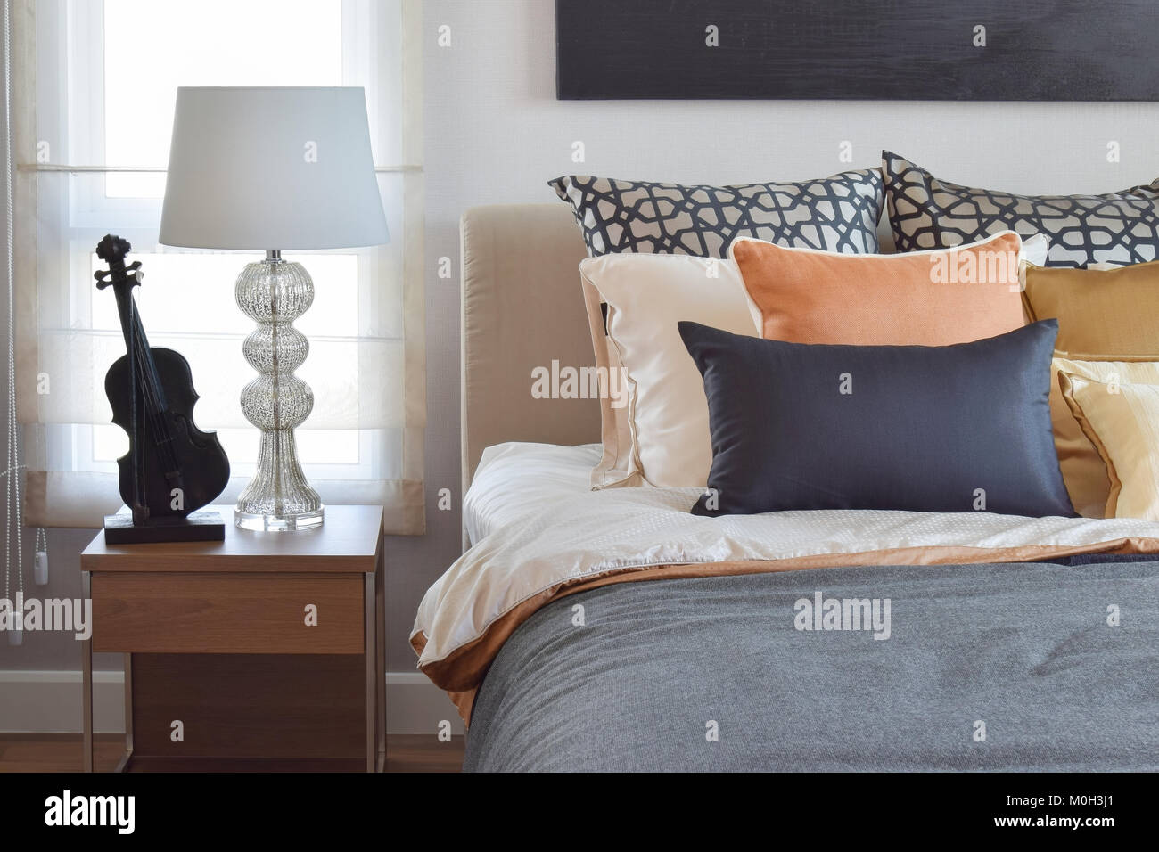modern bedroom interior with orange and gold pillows on bed ...