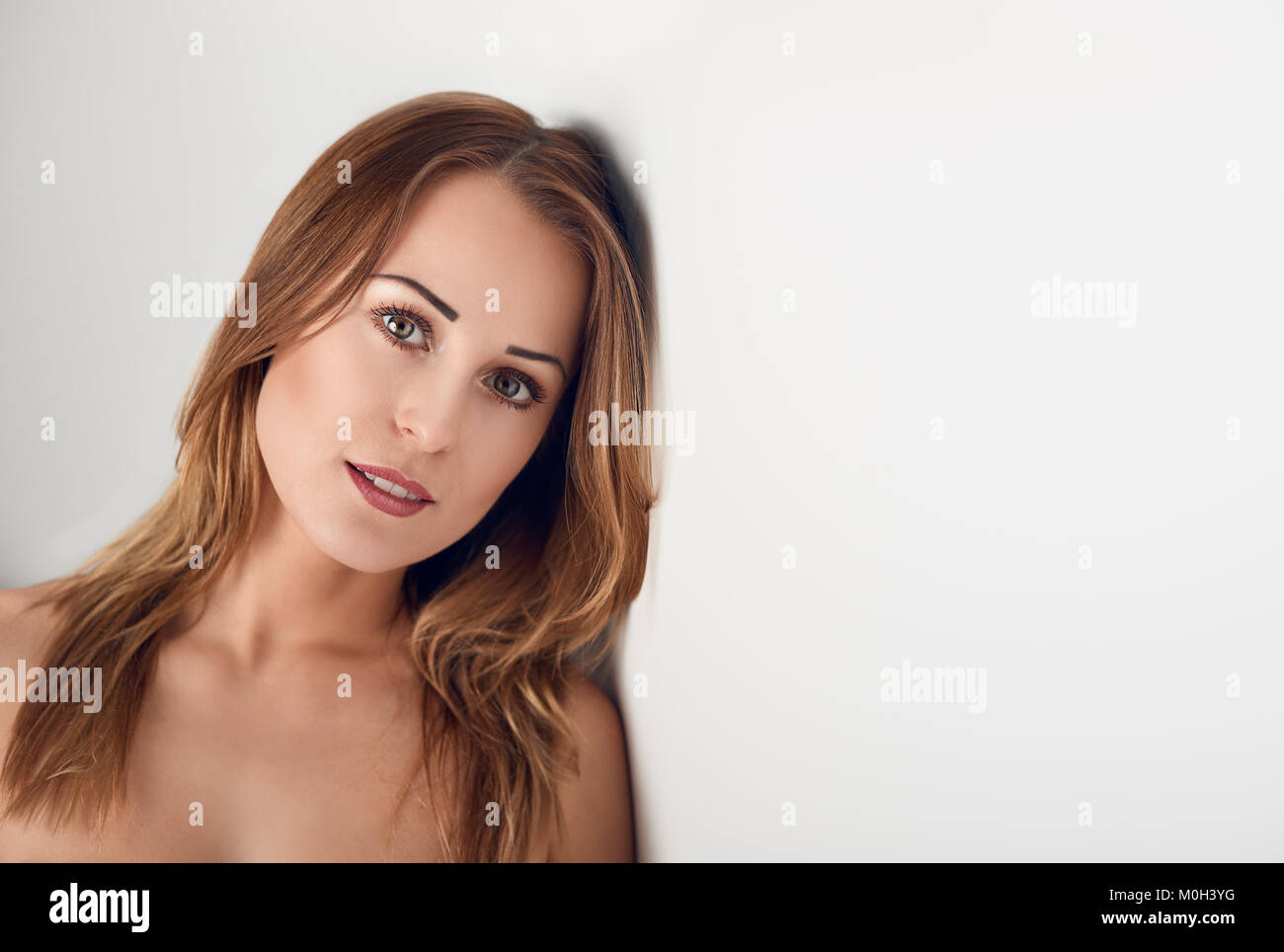Young woman with pretty smile looking at camera over her bare shoulder leaning on white wall with copy space, viewed - Stock Image