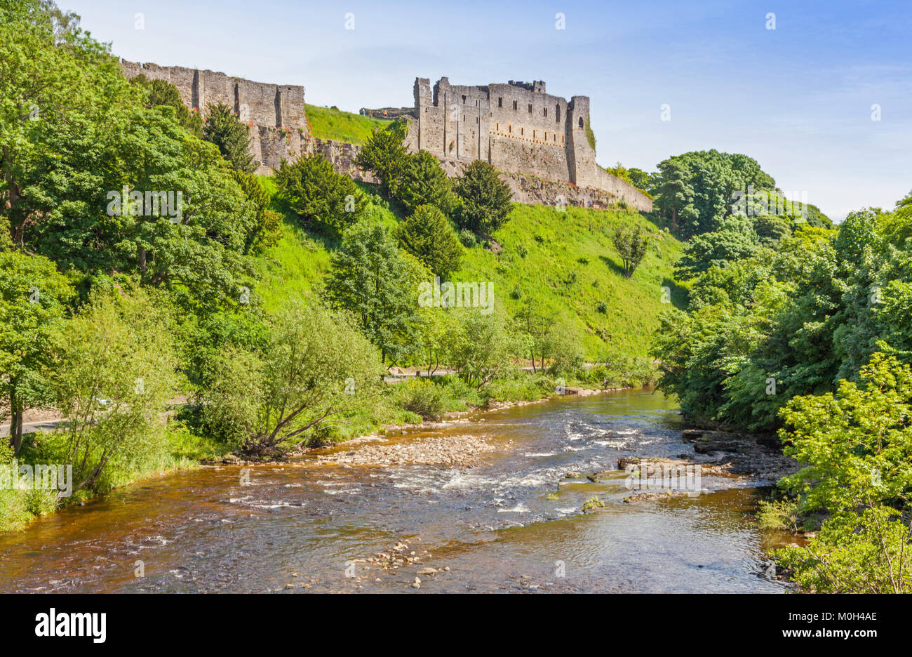A view of the imposing Richmond Castle in Yorkshire, England, with the River Swale in the foreground. - Stock Image