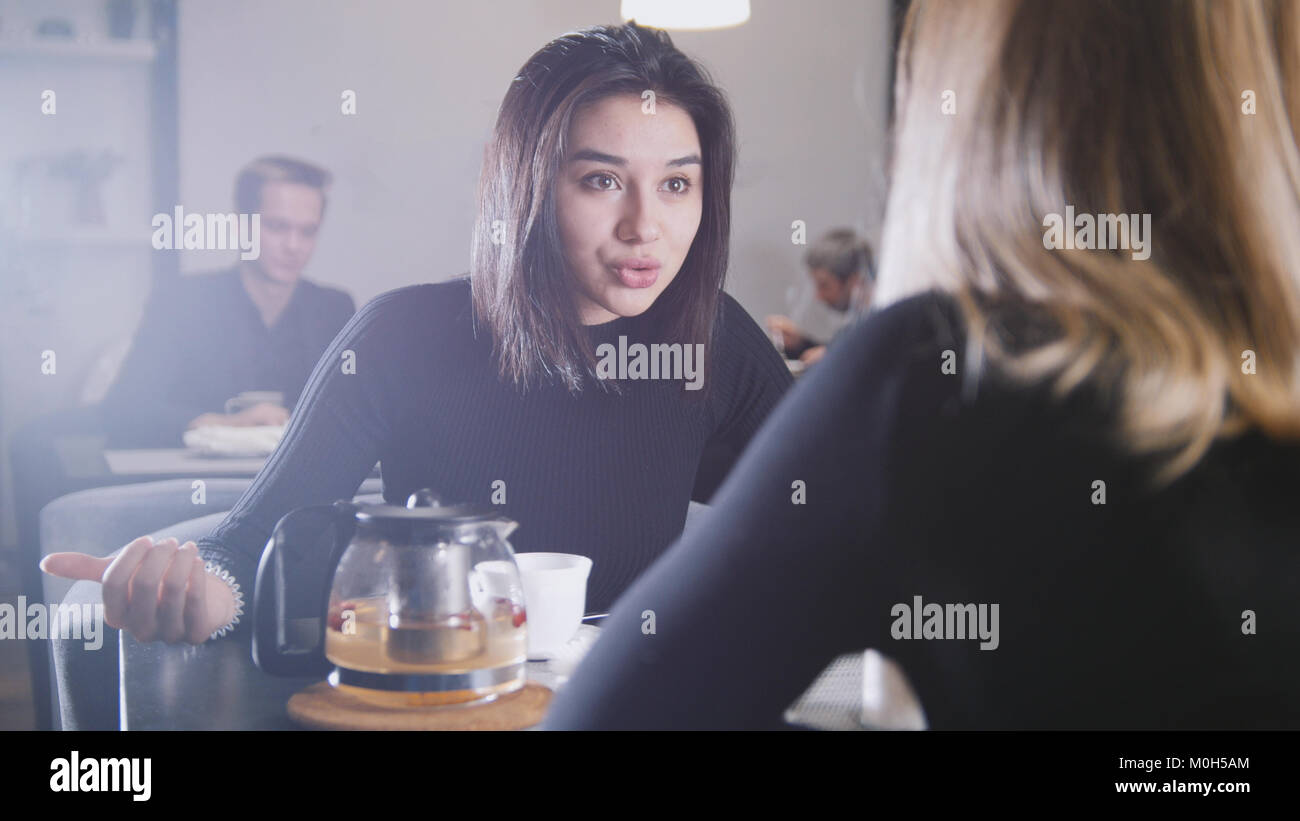 Black haired young woman with black hair drinking coffee and talking with girlfriend in the cafe - Stock Image