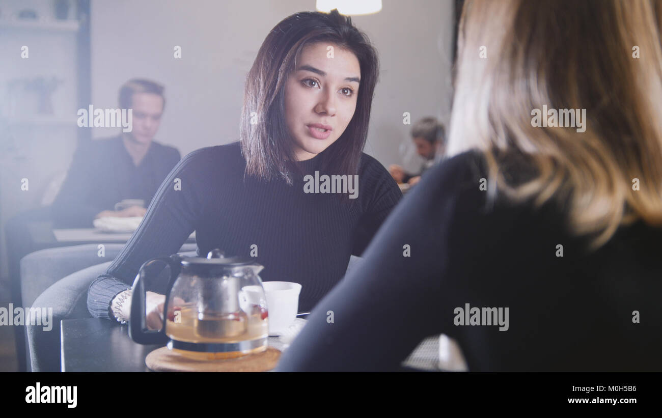 Pretty young woman with black hair drinking coffee and talking with girlfriend in the cafe - Stock Image