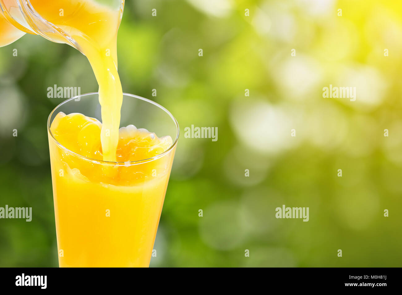 pouring orange juice - Stock Image