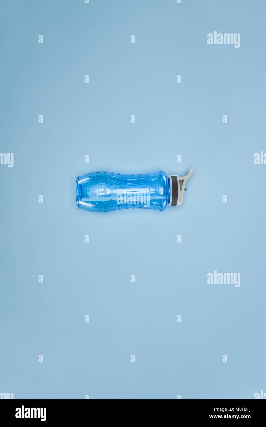Sports water bottle isolated on blue background - Stock Image