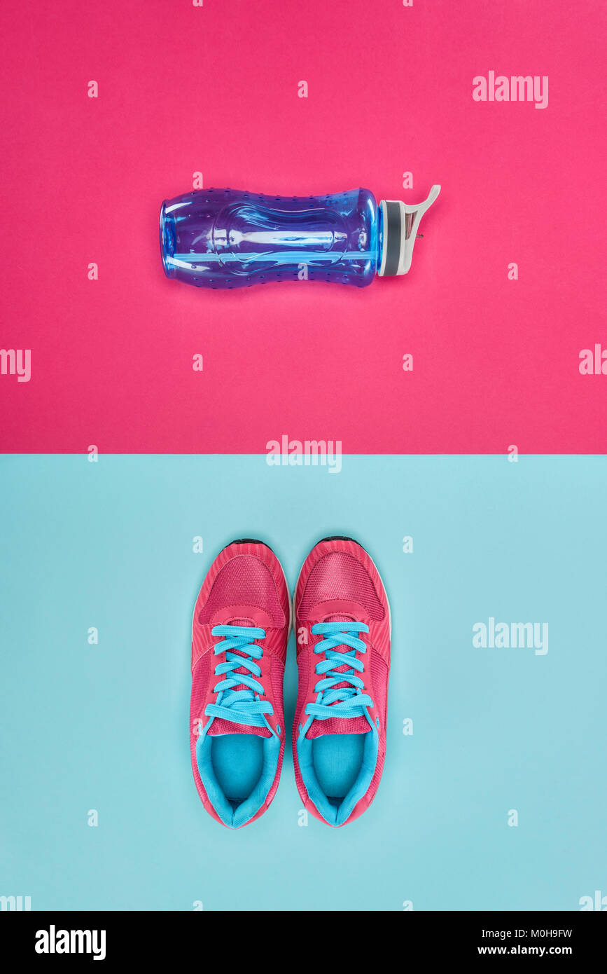 Sports equipment with shoes and water bottle isolated on pink and blue - Stock Image