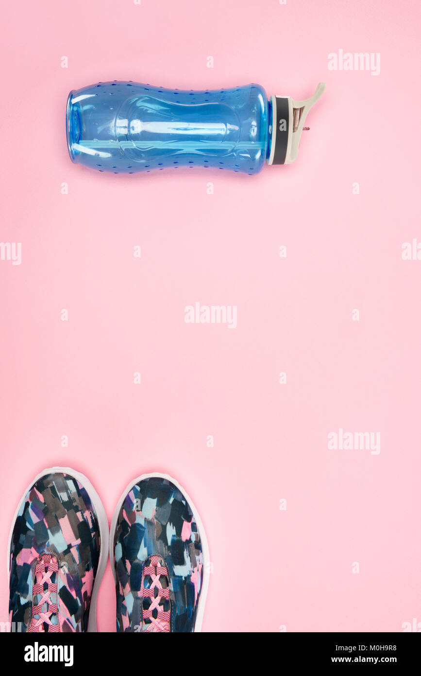 Sports shoes and water bottle isolated on pink - Stock Image