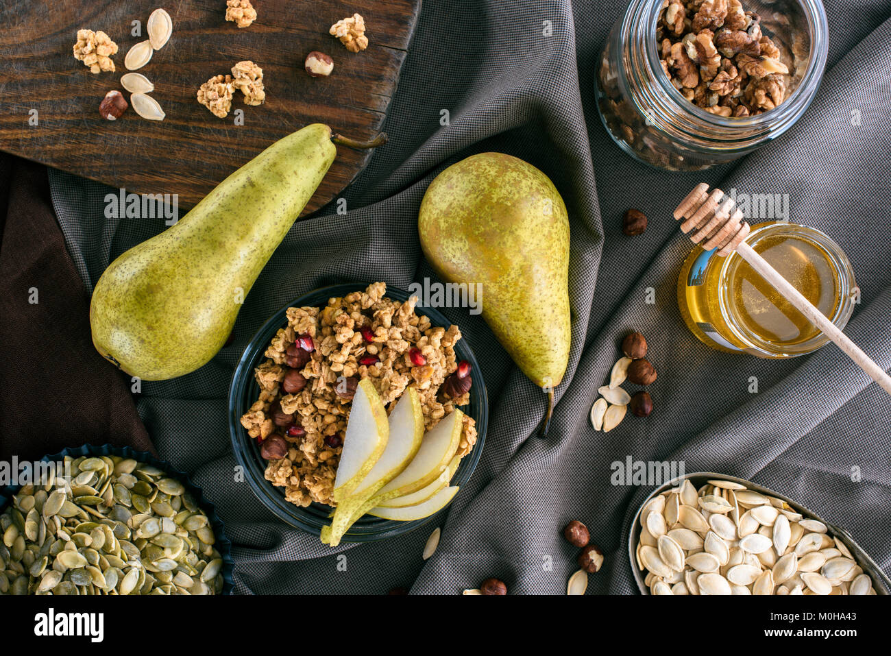 top view of pears, honey and homemade granola on tabletop - Stock Image