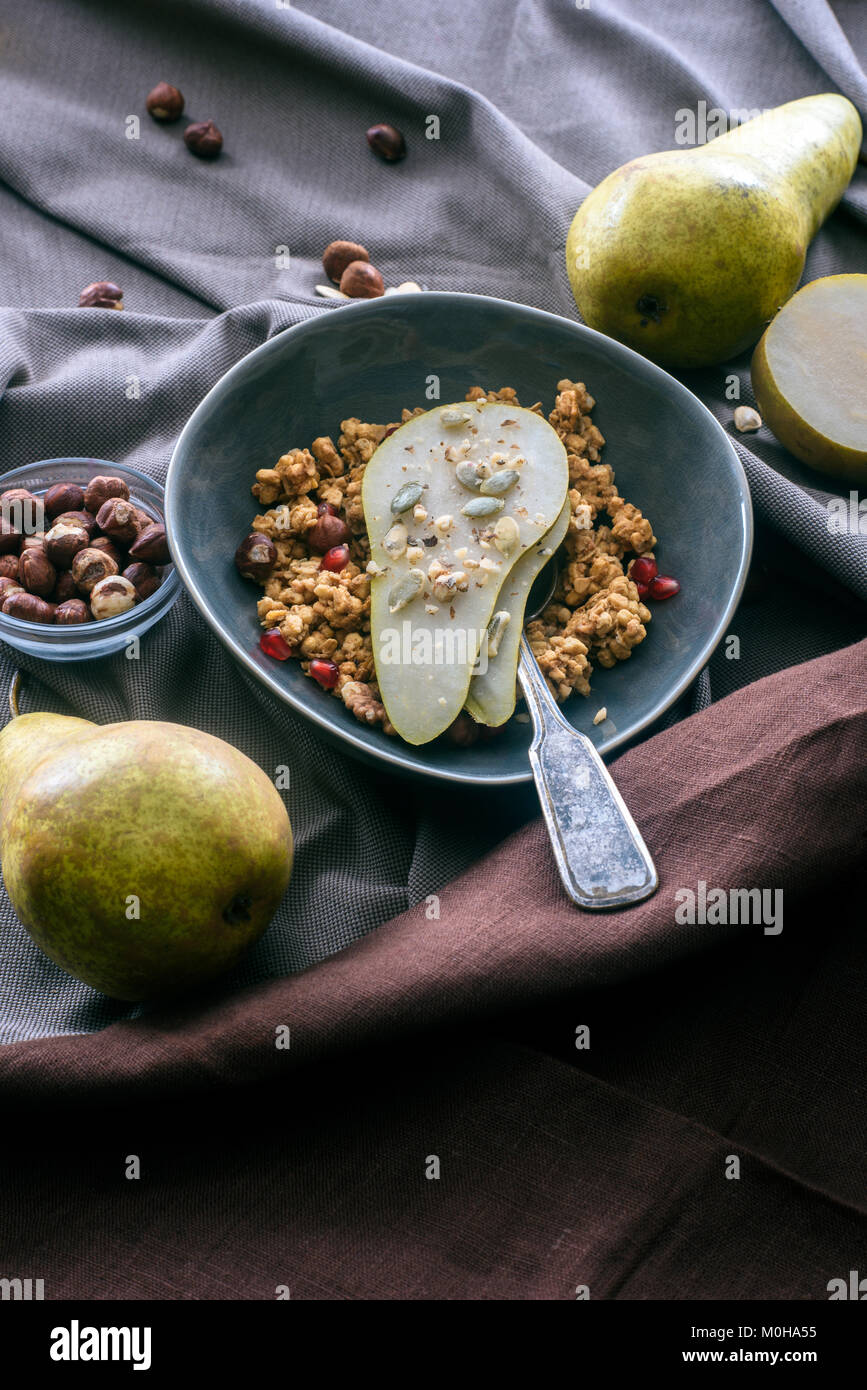 overhead view of bowl with granola and pear on table - Stock Image