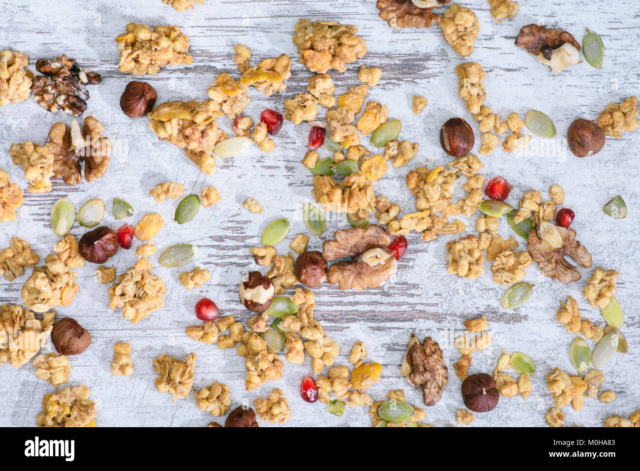 top view of scattered granola with nuts on grungy tabletop - Stock Image