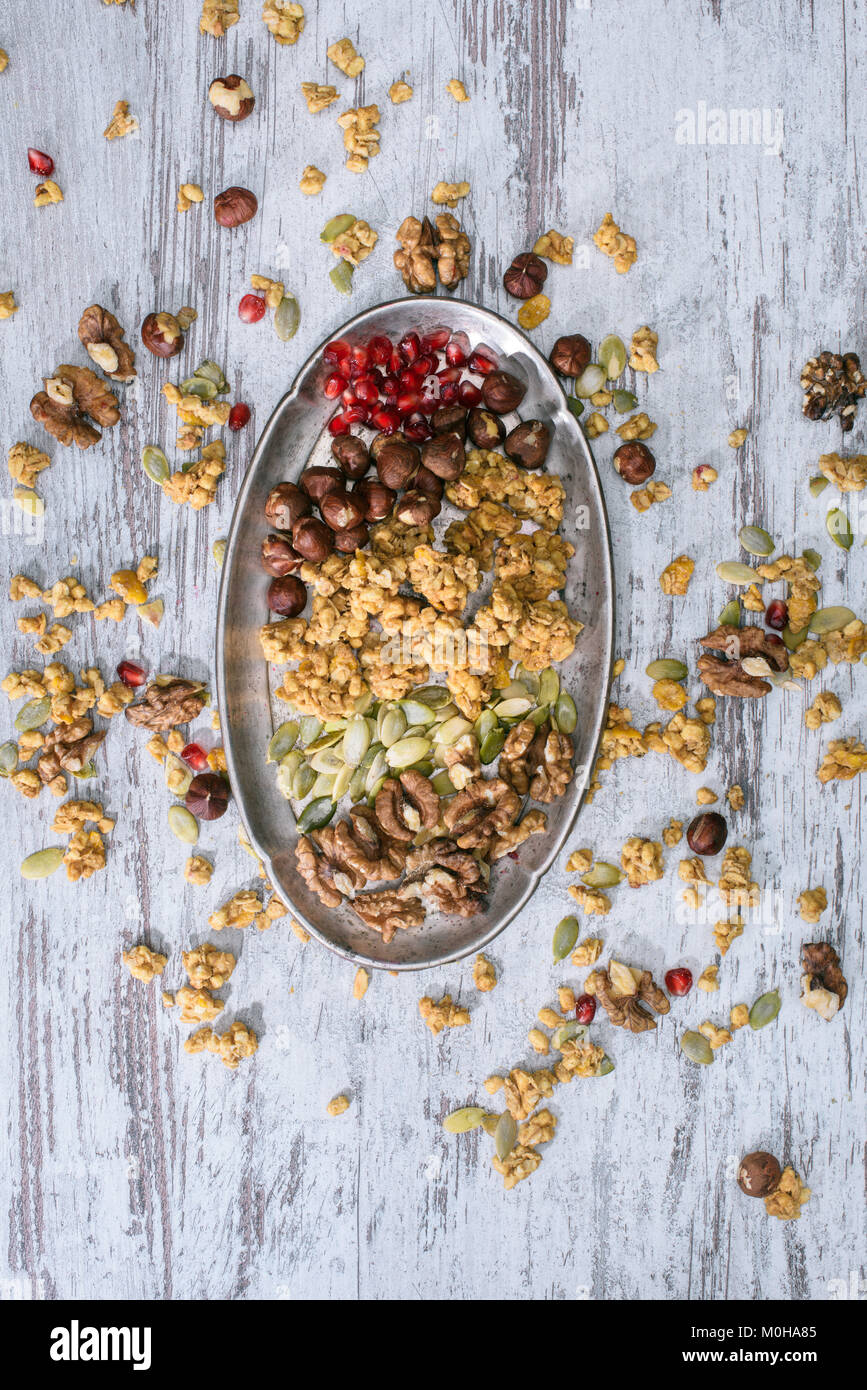 top view of granola ingredients on plate on wooden table - Stock Image