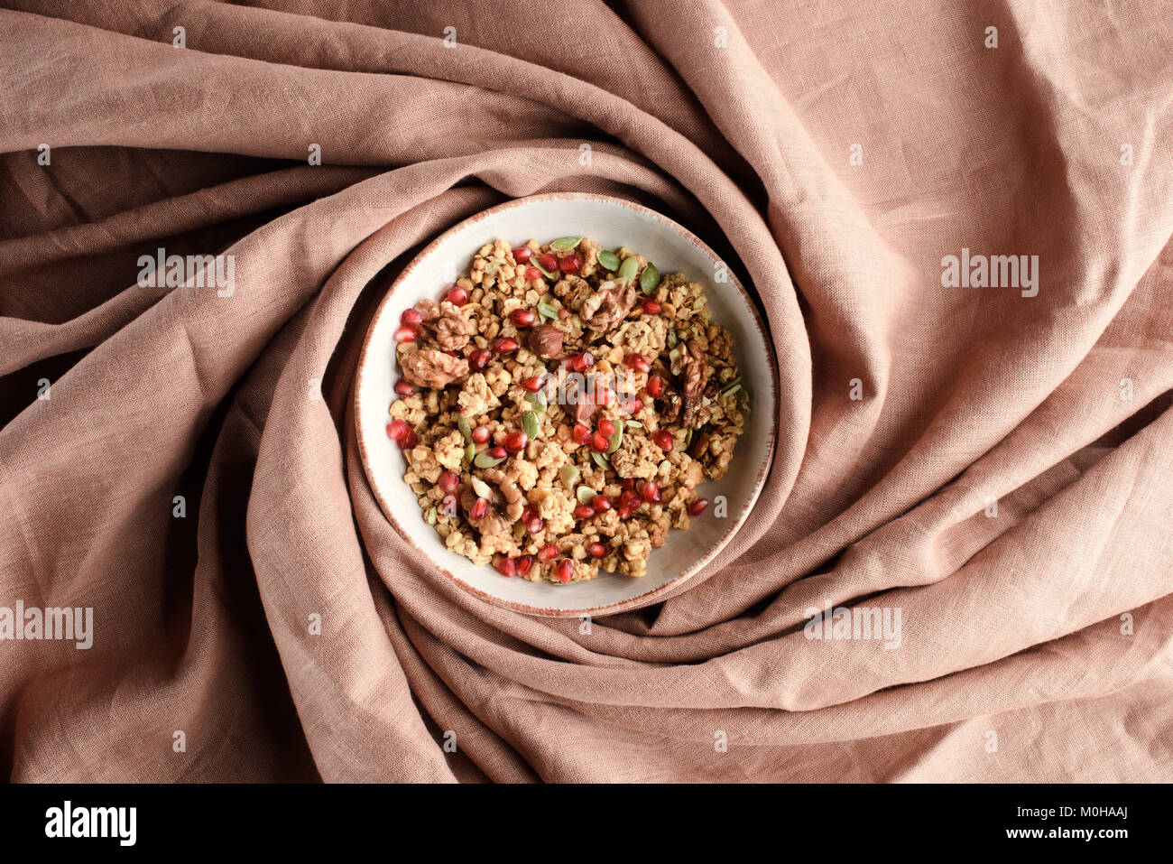 top view of plate with homemade granola on beige tablecloth - Stock Image