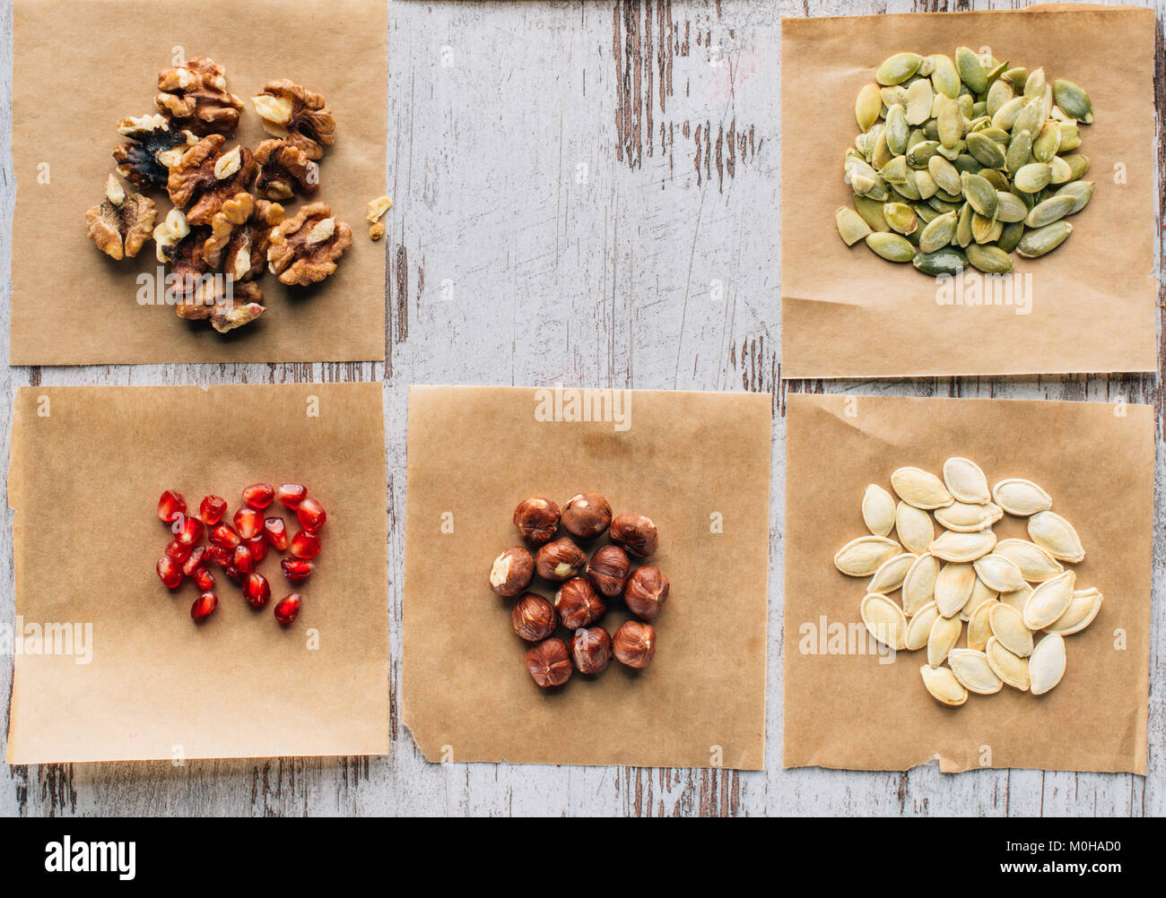 top view of nuts, pumpkin seeds and pomegranate seeds on table - Stock Image
