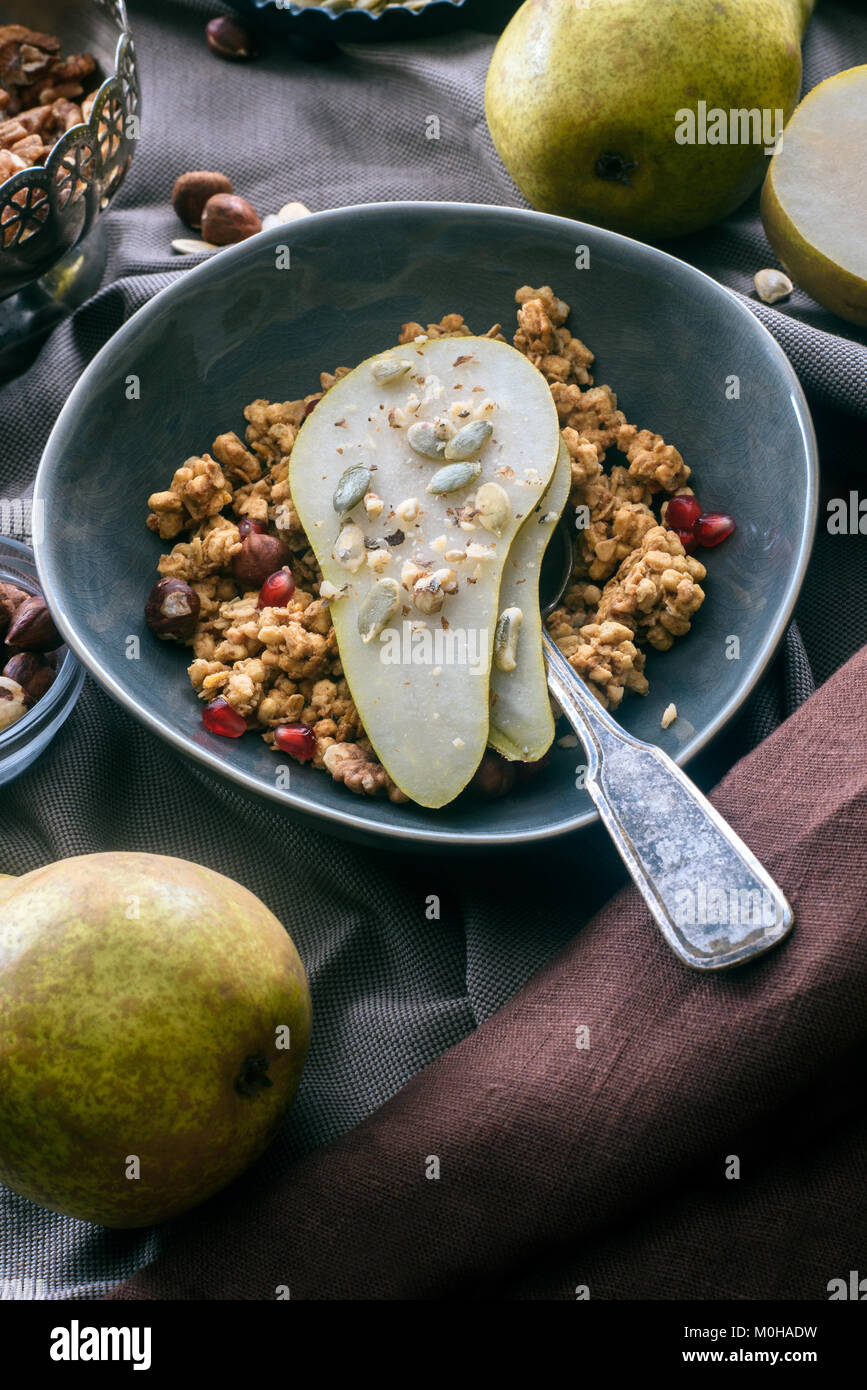 overhead view of granola with pear pieces in bowl - Stock Image