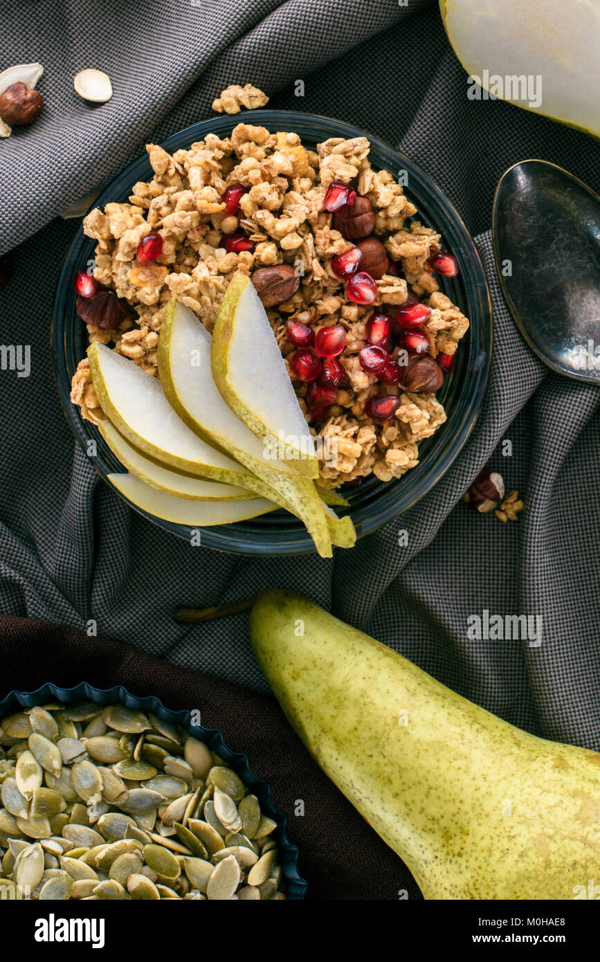 top view of crunchy granola with pears and pomegranate seeds on table - Stock Image