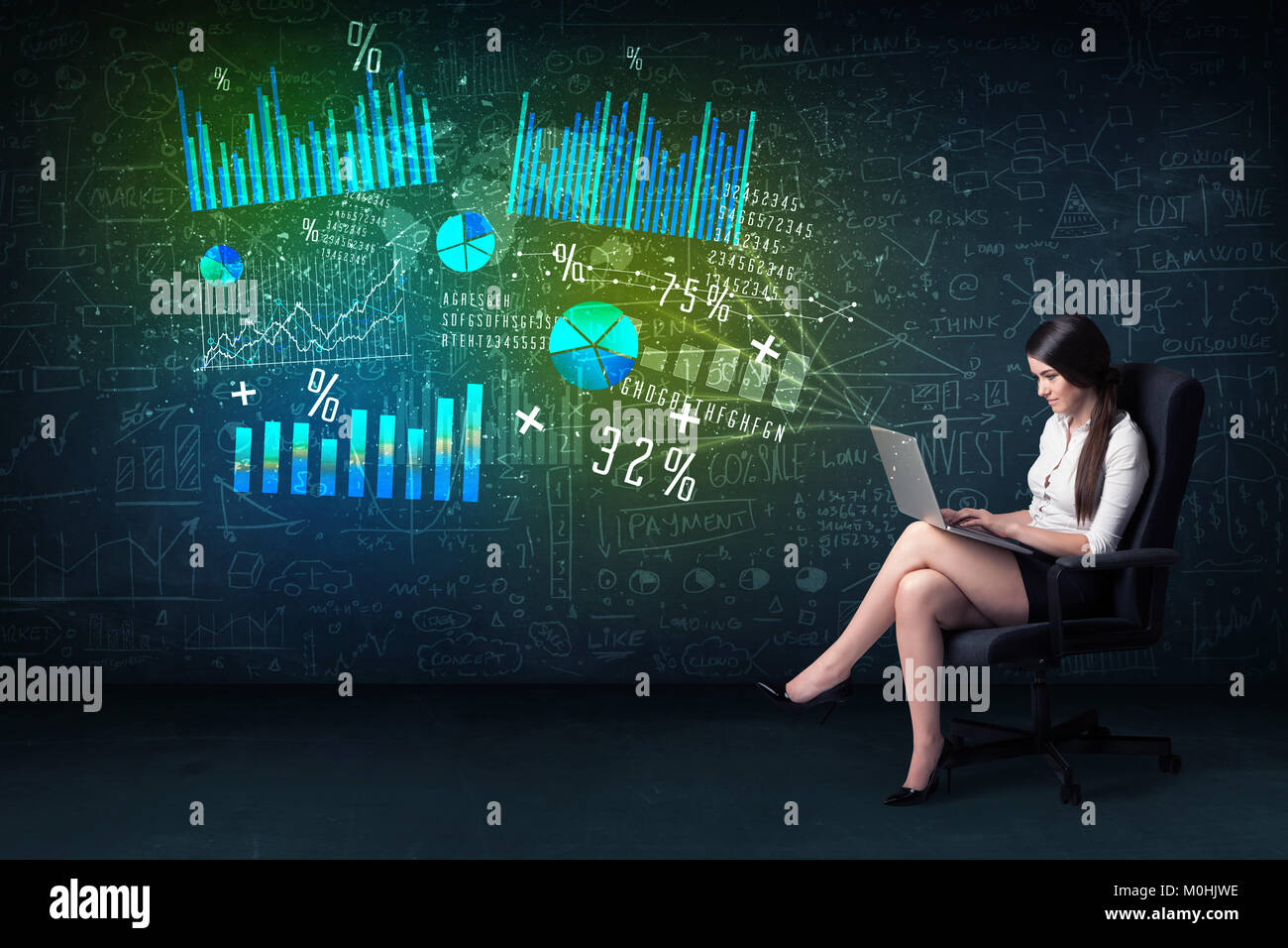 Businesswoman in office with lapotp in hand and high tech graph charts concept on background - Stock Image