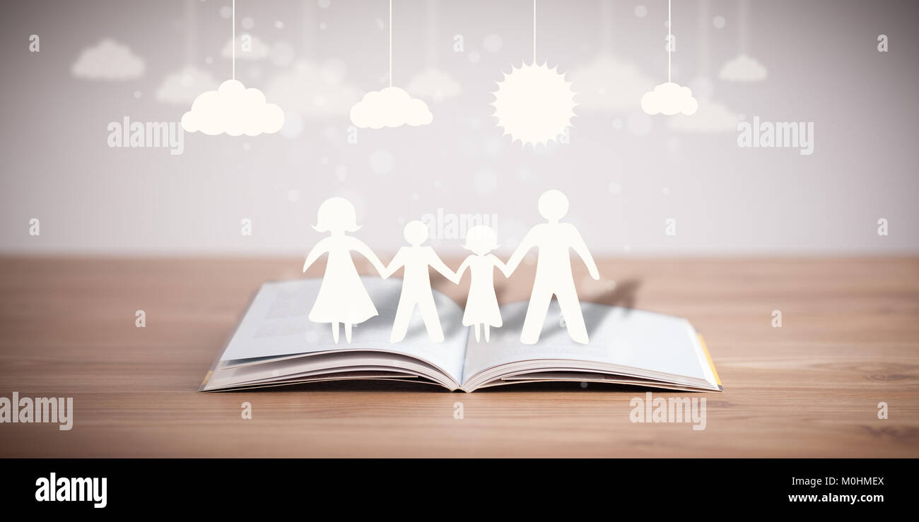 Cardboard figures of the family on opened book. The symbol of unity and happiness Stock Photo