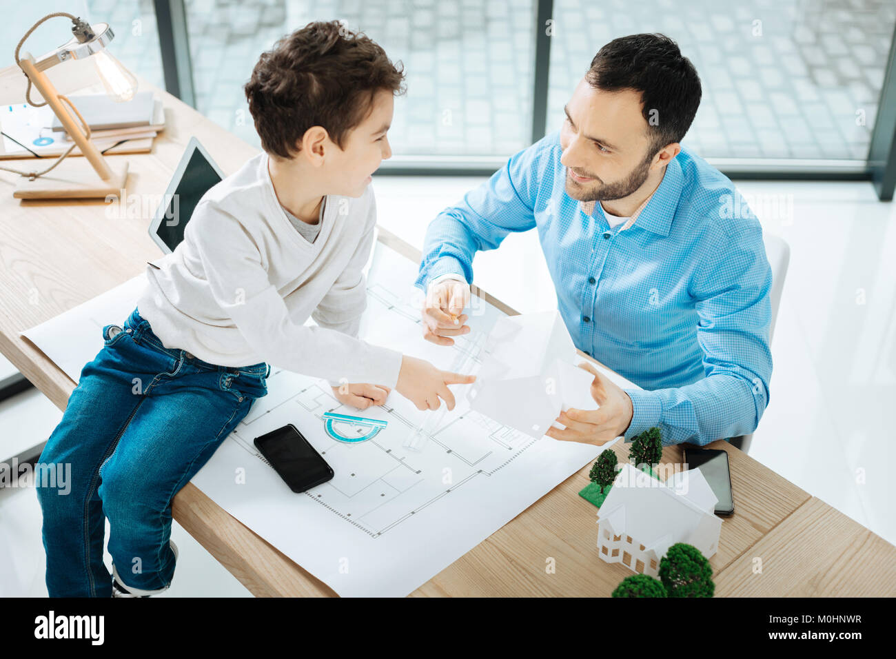 Adorable boy asking his father about house models - Stock Image