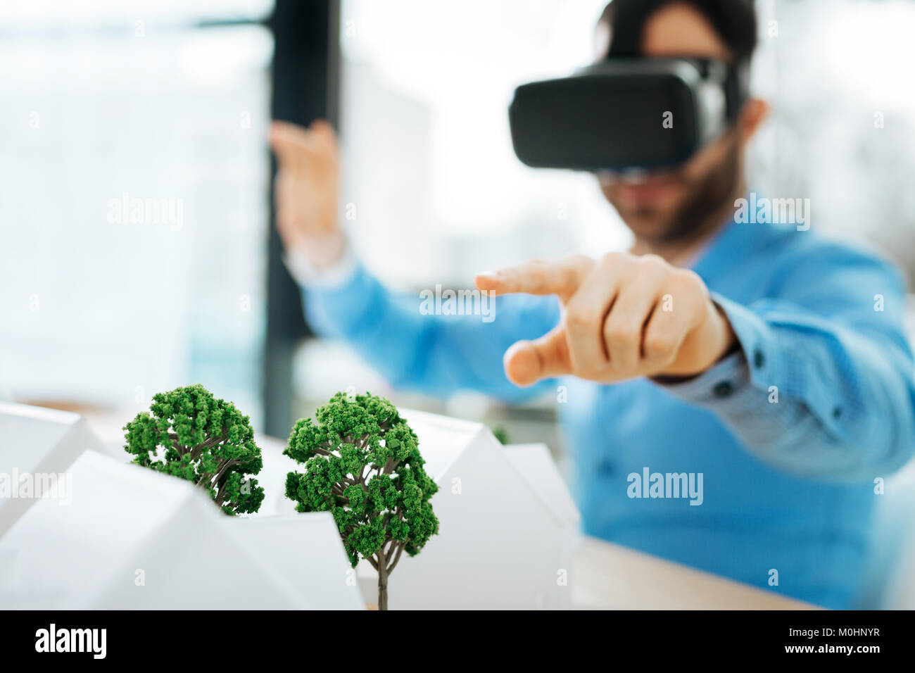 Pleasant architect in VR headset pointing at tree models - Stock Image