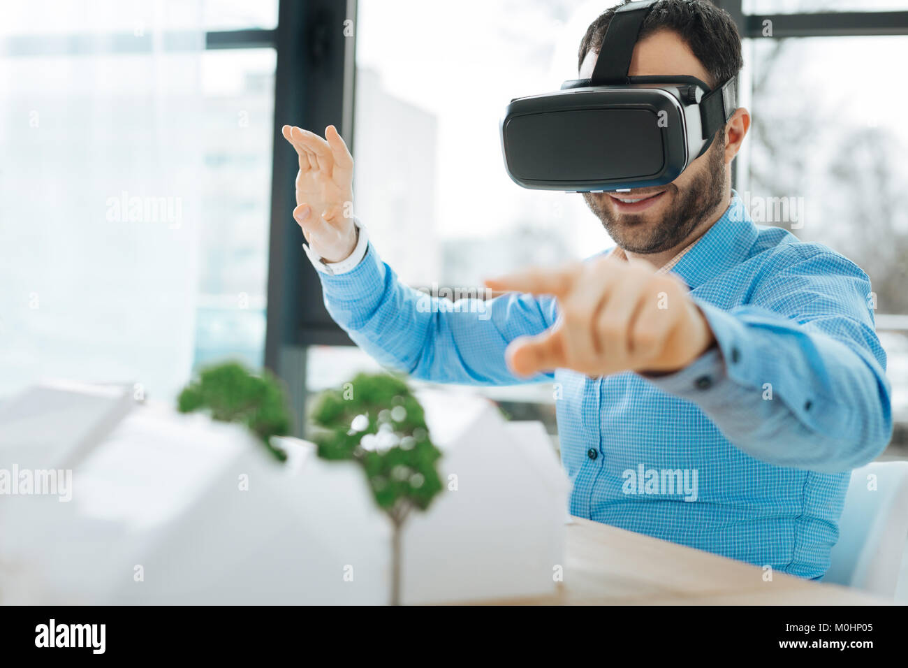 Smiling architect in VR headset pointing at house models - Stock Image