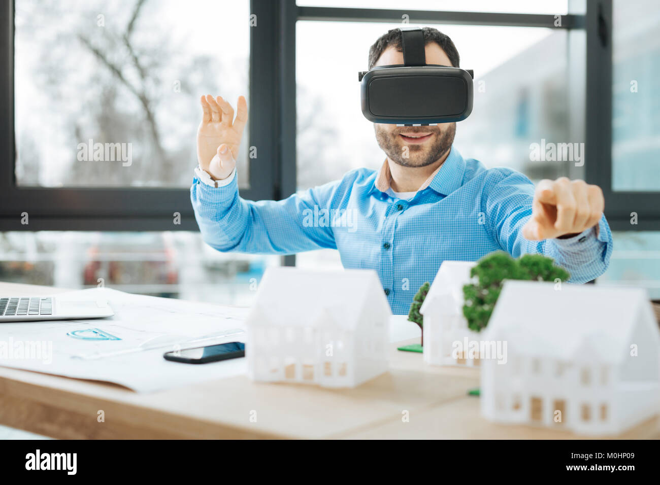 Handsome architect wearing VR headset and pointing at house models - Stock Image
